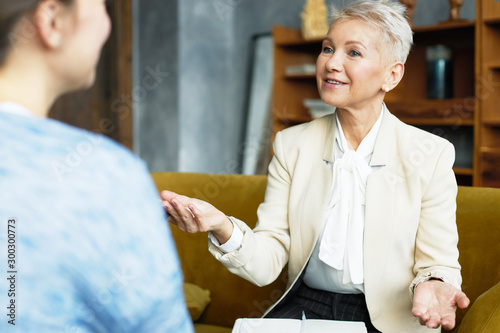 Photo Attractive mature female HR director and job candidate at interview, having lively discussion