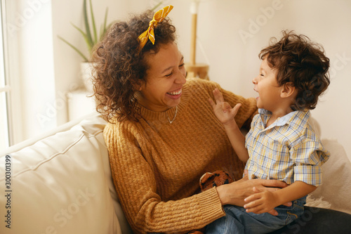 Indoor shot of happy young Hispanic woman with brown wavy hair relaxing at home embracing her adorable toddler son Canvas Print