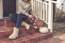 Girl Sitting On The Steps Of The Porch In Front Of The House With Autumn Pumpkins, Basket With Harvest, Concept Of Organic Natural Lifestyle