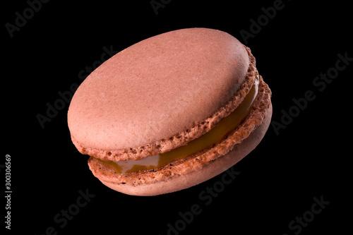Cuadros en Lienzo Macro photo of french caramel macaroon or macaron isolated on black background