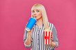 canvas print picture - Portrait of a beautiful young woman holding popcorn and drinking soda isolated on pink background