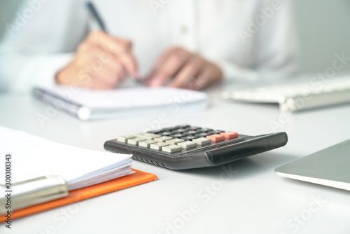 Fotomural  Office table view with out of focus on Accountant, focus on calculator