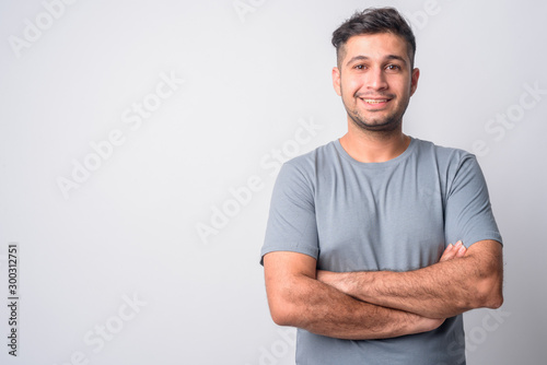Portrait of happy young Persian man smiling with arms crossed Wallpaper Mural