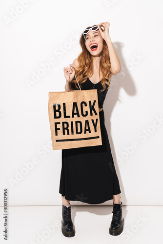 Portrait of laughing woman holding paper bag and using cellphone