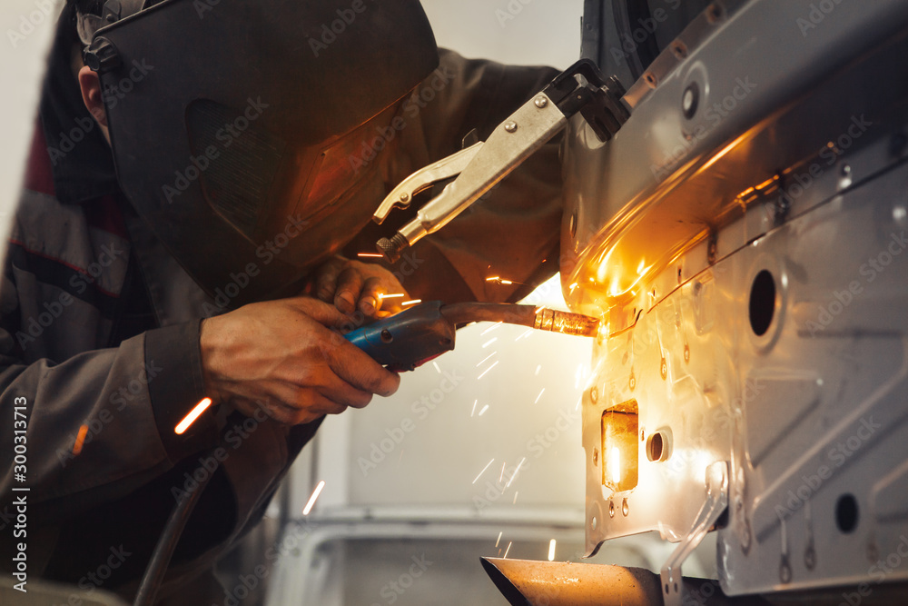 Fototapeta Worker repairing car body with carbon dioxide welding. Weld of auto.