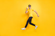 Full size photo of handsome guy jumping high holding paper cup takeaway coffee walking down street wear sun specs casual t-shirt pants isolated yellow color background