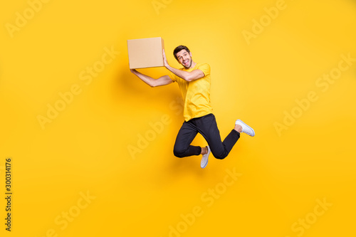 Foto  Full length photo of handsome guy jumping high holding big carton box moving to