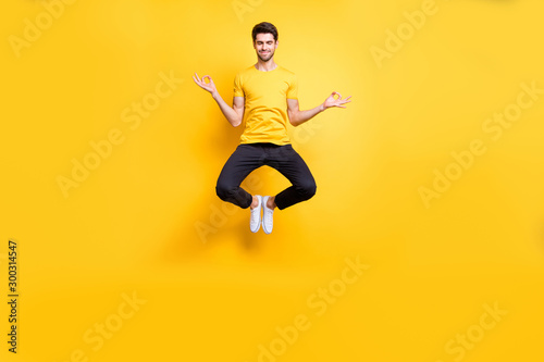 Full body photo of handsome guy jumping high lotus position morning yoga training relaxing fingers together wear casual t-shirt black trousers isolated yellow color background