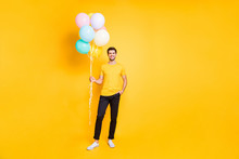 Full Length Photo Of Handsome Guy Holding Many Air Balloons Meeting Guests At Summer Students Party Wear Casual T-shirt Black Trousers Isolated Yellow Color Background