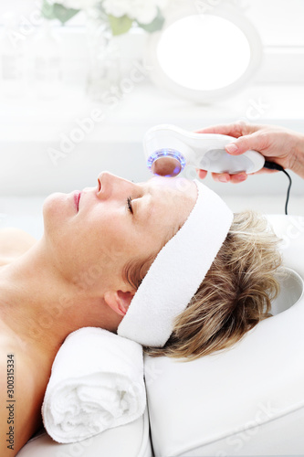Photonic ultrasonic facial massage. Ultrasonic facial massage using light therapy. Professional treatment in a cosmetics clinic.