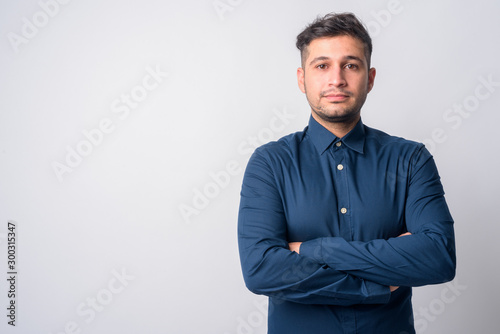 Portrait of young handsome Persian businessman with arms crossed