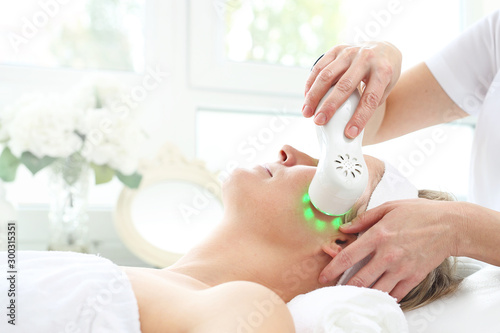 Ultrasonic facial massage, light phototherapy. Ultrasonic facial massage using light therapy. Professional treatment in a cosmetics clinic.