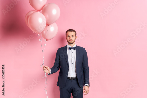 Valokuva Sad male wearing formal suit hold pink balloons isolated over pink background