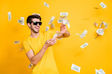 Photo Of Young Handsome Careless Guy Throwing Usa Money Banknotes Away Wealthy Person Wear Sun Specs Casual T-shirt Isolated Bright Yellow Color Background