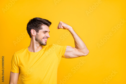 Fotografía  Photo of young handsome guy holding fist raised demonstrating perfect big biceps