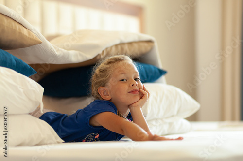 Little cute girl built impromptu fort (castle, house) out of pillows and blankets on bed Slika na platnu