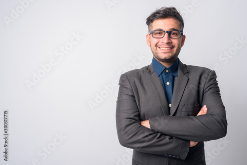Fotografía  Portrait of happy young Persian businessman in suit smiling with arms crossed