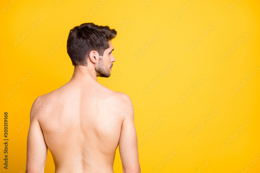 Fototapeta Rear behind profile view photo of handsome guy showing perfect spine muscles looking seriously empty space naked isolated yellow color background