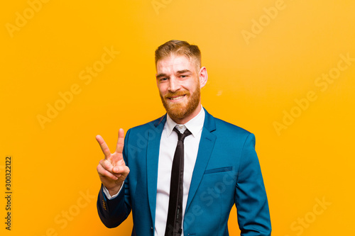 Pinturas sobre lienzo  young red head businessman smiling and looking friendly, showing number two or s