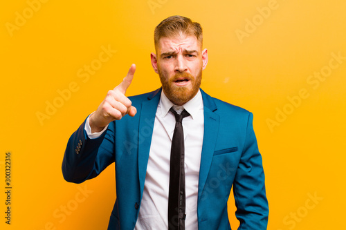 Valokuva young red head businessman pointing at camera with an angry aggressive expressio