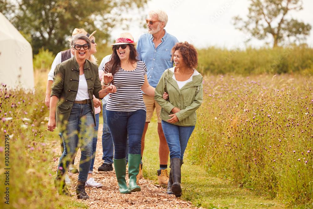 Fototapeta Group Of Mature Friends Walking Along Path Through Yurt Campsite