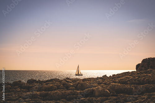 Fotografía  Sail boat in beautiful sunset at sea