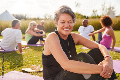 Fototapeta Portrait Of Mature Woman On Outdoor Yoga Retreat With Friends And Campsite In Ba