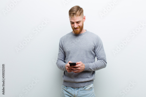 Obraz young red head man with a smart phone against white background - fototapety do salonu