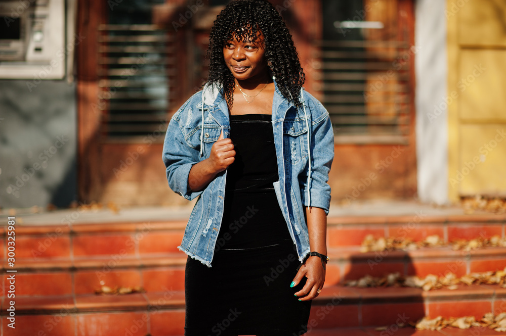 Fototapeta Stylish trendy afro france curly woman posed at autumn day in jeans jacket. Black african female model.