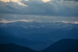 Fototapeta Do pokoju - snow mountain peaks stick out on the horizon under the clouds