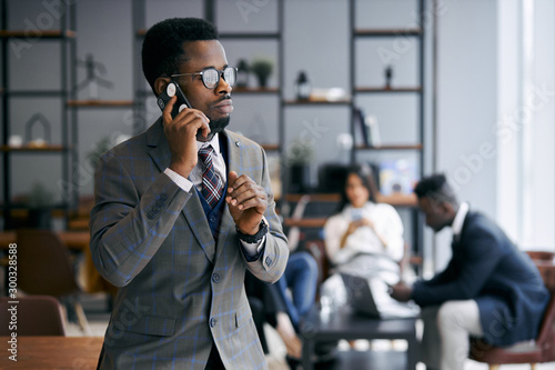 obraz lub plakat Black businessman wearing grey tuxedo using smartphone during work time in modern office talking with colleague on phone, business partners meeting background. Business people concept