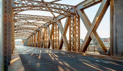 Asfaltna cesta ispod čelične konstrukcije mosta u gradu za sunčanog dana. Večernja urbana scena sa sunčevim zracima u tunelu. Koncept gradskog života, prometa i prometa.