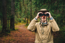 A Man In A Hat And Uniform Green And Beige Holds Binoculars And Looks Into The Distance, Ranger Watching The Territory, The Protection Of The Reserve