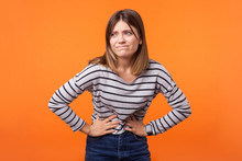 Portrait Of Unhappy Ill Woman With Brown Hair In Long Sleeve Striped Shirt Standing, Holding Her Belly With Hands, Stomach Cramps Or Period Pain. Indoor Studio Shot Isolated On Orange Background