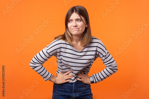 Portrait of unhappy ill woman with brown hair in long sleeve striped shirt standing, holding her belly with hands, stomach cramps or period pain Fototapeta