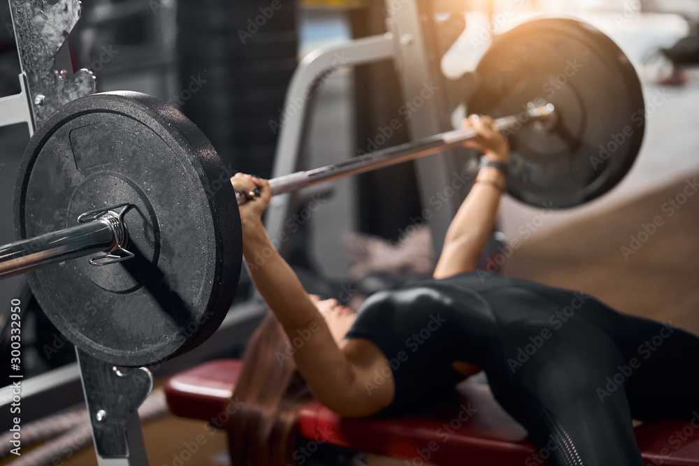 Fototapeta Close up of black iron barbell with heavy discs in hands of strong female weightlifter lying on red bench, attempting to do bench press in modern fitness club, side shot