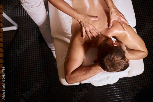 Valokuva  Gentle female hands giving deep tissue massage to young male client, man having