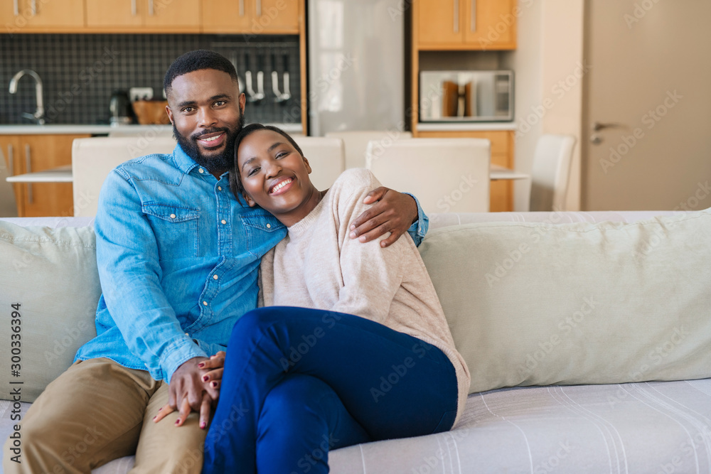 Fototapeta Smiling young African American couple relaxing together on their sofa