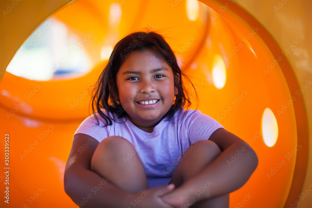 Fototapety, obrazy: A nine year old girl having fun playing in a yellow playground slide.