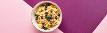 Top View Of Bowl With Breakfast Cereal And Blueberry On Purple And Pink Background, Panoramic Shot