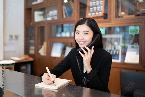 Billede på lærred Welcome to the hotel,Happy young Asian woman hotel receptionist worker smiling s