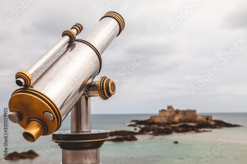 Papiers peints Affiche vintage Tourist monocular telescope on the terrace of Saint Malo opposite the Fort National fortress