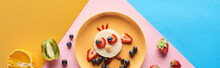 Top View Of Plate With Fancy Animal Made Of Food For Childrens Breakfast On Blue, Yellow And Pink Background