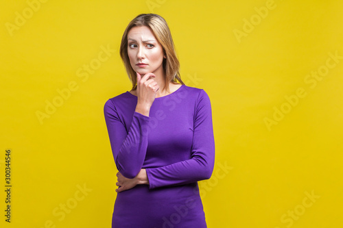 Fototapety, obrazy: Portrait of confused puzzled woman in tight purple dress standing holding her chin and looking aside while thinking intensely, having doubts suspicion. indoor studio shot isolated on yellow background