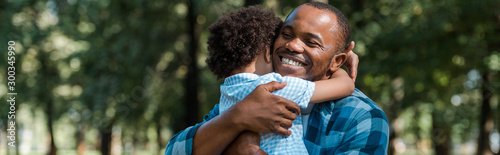 Obraz panoramic shot of happy african american father hugging son - fototapety do salonu