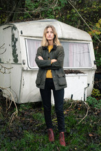 Blonde Woman Standing In Front Of Old Camper