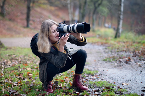 Obraz Blonde photographer squatting and using camera with large telephoto lens while taking shots in nature - fototapety do salonu