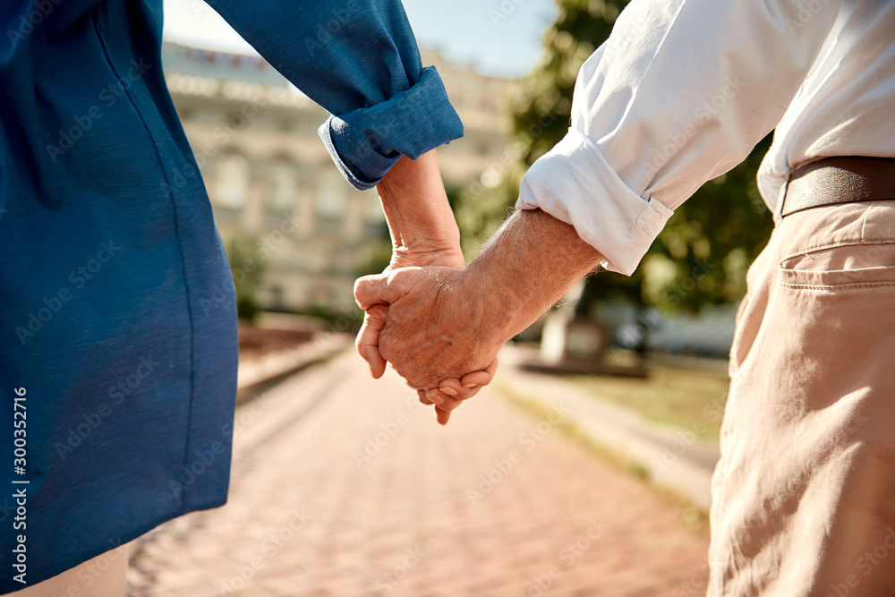 Fototapety, obrazy: You and me forever. Close-up of elderly couple holding hands while walking together outdoors