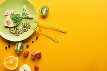 Top View Of Plate With Fancy Fish Made Of Food Near Fruits And Cutlery On Colorful Orange Background