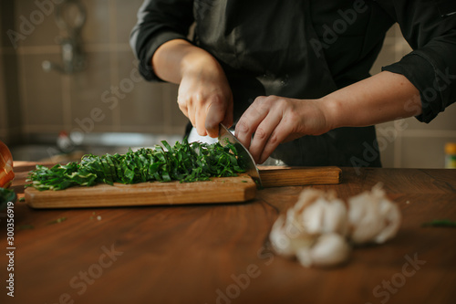 Closeup of female chef's hands preparing a recipe in the kitchen with vegetables. Woman cook chopping spinach leaves for vegetarian dish.